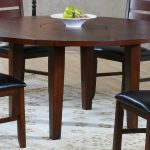 round wooden drop leaf dining table for small spaces with black and wooden chairs plus modern rug in floral motif plus wooden floor and fresh fruits