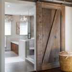 rustic sliding barn door design with white sliding metal rod idea before bathroom with wooden floring with rattan basket