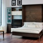Rustic Wooden Fold Up Wall Bed Design With White Sheet Between Wall Storage Design Aside Cream Setaing Beneath Glassy Floor To Ceiling Glass Window Upon Hardwood Floor