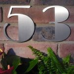 silver art deco house numbers on brick wall plus plants