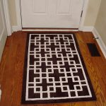 simple brown entry way rugs with white wooden entry door plus wooden flooring for modern house