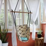 simple chairs that hang from ceiling with cute motif plus white curtain and warm rug plus rattan table and plant pot plus glass windows