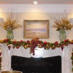 simple christmas decorations for mantels fireplace with garland and colorful baubles plus ribbon snd painting on wall and twin ceramic vases