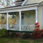Simple Country Home Style With Wrap Around Porch Addition That Is Completed With Wood  Railings In White A Set Of Furniture And Decorative Hang Plants