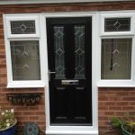 simple hinged wood screen door in black color with larger sidelights and crafted glass panel