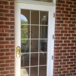 simple screen door with white wood trims and molds red bricks wall system