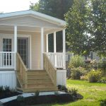 small front porch with white wood fence railing and natural tone color wood stair railing for mobile home