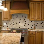 small mosaic tile groutless backsplash idea beneath natural wooden cabinetry design with marble top and island beneath vintage pendants