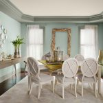 soft blue color for dining room wall  large console table for putting some decorative items  arrangement of decorative plates on wall a set of dining furniture white rug with beautiful patterns