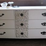 sophisticated sideboard with drawers and ornament on it plus vintage handles and dark flooring