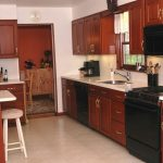 strong wooden burgundy kitchen cabinet with black appliance and white countertop facing narrow kitchen bar