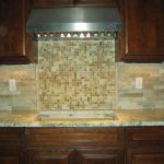 stunning natural tone groutless backsplash design with mosaic small tiles beneath woden cbainetry with marble countertop