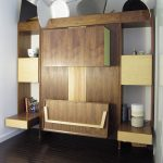 Stunning Natural Wooden Fold Up Wall Bed Design With Standing Storage Idea Beneath White Wall Upon Dark Laminated Flooring