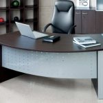 u shaped desk design with brown glossy top with black leather swivel chair with tall backrest with wall storage