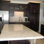 u shaped kitchen design with black wooden cabinetry and large island with white cashmere granite countertop
