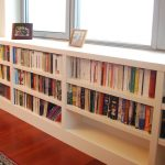 under window bookcase in white with a lot of book arrangement and family framed pictures plus wooden floor and red rug