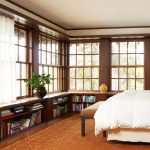 under window wooden bookcase in bedroom ideas with greenery and large brown rug area and comfy bedding set