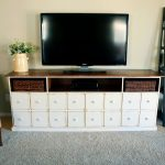 unique  tv console  with drawers for storage and flower vase and grey rug plus armchairs