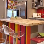 unique wooden kitchen island design with colorful vertical stripa patterned decoration with red acrylic backsplash and acrylisc chairs and floral patterned pendants