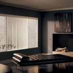 vinyl graber blinds vertical and horizontal with black tufted bed and wooden flooring and painting on wall decoration plus wooden table