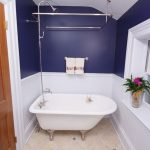 white ceramic bathtub with showers and towel holder in blue wall scheme and tiled floor in small bathroom ideas