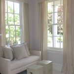 white inverted pleat drapes for glass windows plus comfy white sofa with cushions plus wooden box tables for living room decoration