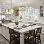 white kitchen design with white cabinetry and white kitchen island with brown wooden chairs beneath luxurious pendants upon gray tile flooring idea