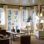 window treatments for wide windows in living room with glass window and glass door and white chair and fireplace and soft rug and end table