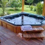 wonderful geometrical built in hot tub design with wooden deck with wooden pillars with wooden staircase aside greenry