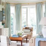 wonderful window coverings for bay windows in living room with blue curtain and ivory sofa plus coffee table plus bookshelf and end table