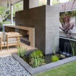 wondrous outdoor landscape design with small rectangle ponds and grassy meadow and pebbles and beige seating and concrete wall and fireplace