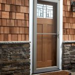 wood screen door with upper glass panel half way wood wall system with natural stones as the base wall single entryway lighting fixture