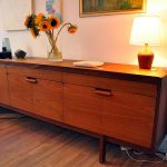 wooden sideboard with sunflower vase plus decorative table lamps and wooden floor plus painiting on wall decoration