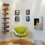 A decorative reading chair in bright green color some decorative picture frames  built-in gas fireplace unit unique floating vertical book shelves made from wood a metal wire basket for storing magazines