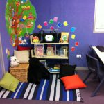 A reading nook for kids consisting a rattan box as bench plus pillows colorful rug with strip pattrern mini book shelves a computer desk with chair