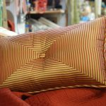 A throw pillow with gold and red strips motif for its cover