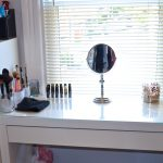 A vanity organization in white with small free standing mirror some decorative glasses for organizing the face brushes a drawer system