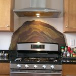 Artistic concrete backsplash with different tone natural colors a gas stove and top kitchen cabinets