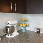 Artistic white kitchen backsplash black stained wood cabinets brown granite kitchen counter modern mixer a decorative fruits storage an arrangement of recipe books and there small containers for spicy