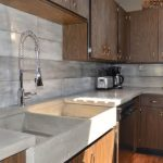 Attractive concrete kitchen backsplash with gloss cement countertops with double sinks and faucet and also wooden kitchen cabinets