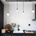 Ball lamps in different height as the light fixtures for sink a block butcher as the cutting board black countertop black cabinets system white ceramic tiles backsplash