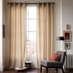 Base to top curtains in soft brown color a corner chair with pillow a standing lamp some decorative frames