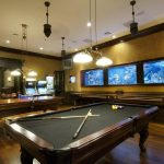 Basement decorating idea for game and entertainment room with two classic pendant lamps and billiard yard table hardwood flooring