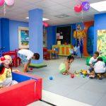 Basement interior decorating for kids' playground with ball pool blue and red kids' chairs and table the furniture in multiple colors white ceramic tiles floor