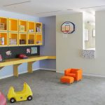 Basement shelving system idea in bright yellow color with yellow standing desk a basket for ball a set of small furniture in orange color some kids' toys