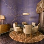 Beautiful purple color for dining room's wall with artistic tree sketch gold tone color window curtain rounded brown rug a set of dining furniture a console table with drawers with table lamp