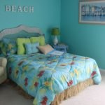 Blue ocean wall paint for beach themed bedroom a bed furniture with blue headboard blue bedding blue bedside table with table lamp a reading chair in brown a painting with light brown frame