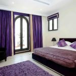 Bold purple curtains for glass door queen sized bed furniture with white bedding and purple bedcover purple pillows purple wool bedroom rug white ceramic tiles floors a black corner chair