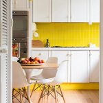 Bright yellow kitchen backsplash white kitchen cabinets a set of simple dining furniture beautiful yellow pendant lamp unfinished wood planks floors