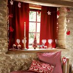 Christmas decoration idea for window in red theme that displays beautiful single chandelier red window curtain some decorative items that are hung on window's top